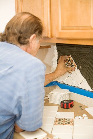 Tile setter uses spacers to carefully apply tiles to the wall.   Stock Photo