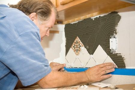 Tile werknemer vaststellen van tegels in de mortel op de muur.