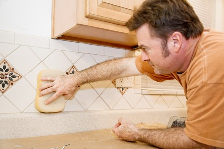 grout: Tile worker wiping grout from a newly tiled kitchen wall.  Focus on hand with sponge.