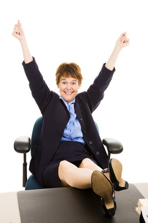 Businesswoman with her feet up on her desk, overjoyed and excited.   photo