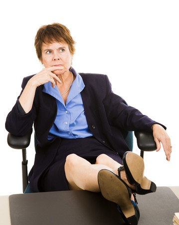 Businesswoman sitting with her feet on the desk worrying.  Isolated on white. photo