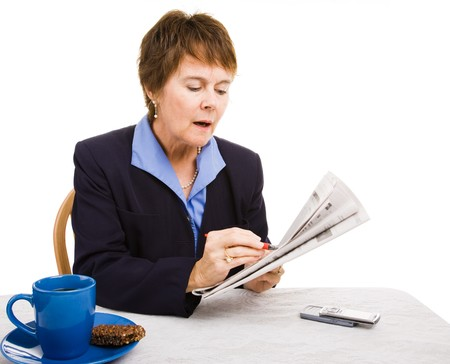 listings: Pretty mature businesswoman circling job listings in the newspaper. Isolated on white. Stock Photo