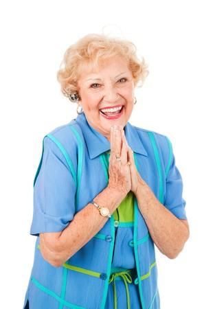 actief luisteren: Extatische senior vrouw krijgt goed nieuws per telefoon, via haar handen vrij ingesteld. Geïsoleerd op wit. Stockfoto