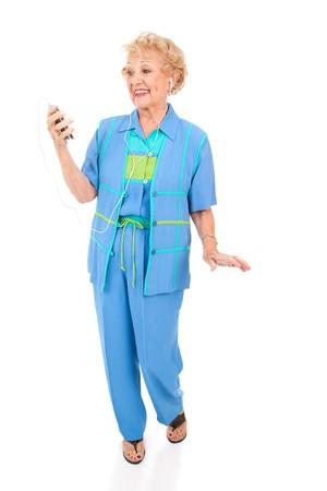 actief luisteren: Actieve senior vrouw dansen op muziek op haar draagbare mp3-speler. Geïsoleerd op wit.