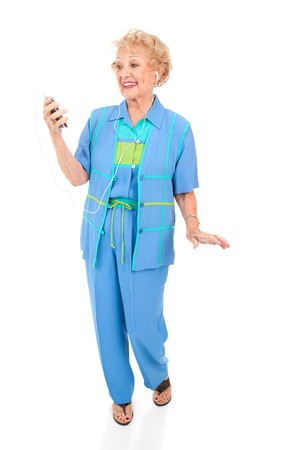portable mp3 player: Active senior woman dancing to music on her portable mp3 player.  Isolated on white.   Stock Photo
