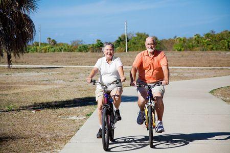 Happy active senior couple riding their bicycles. photo