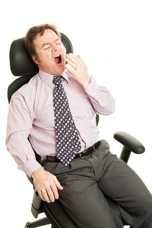 Zakenman yawns in zijn comfortabele ergonomische bureaustoel. Geïsoleerd op wit. Stockfoto