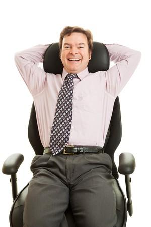 Happy smiling businessman enjoying his new ergonomic office chair.  Isolated on white.   photo