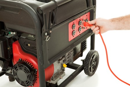 generators: Mans hand plugging an extension cord into an emergency generator.