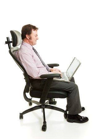 ergonomic: Business man working on his computer in an ergonomic office chair.  Full body isolated on white.