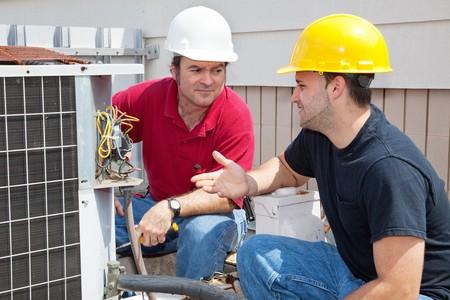 Air conditioning repairmen discussing the problem with a compressor unit.   Banco de Imagens