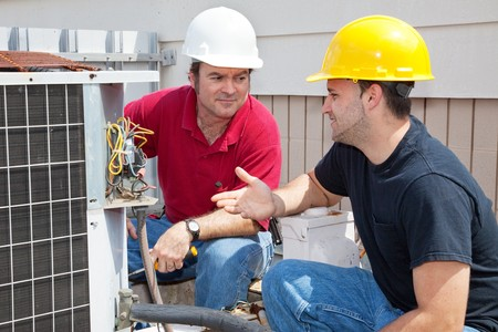 apprentice: Air conditioning repairmen discussing the problem with a compressor unit.   Stock Photo