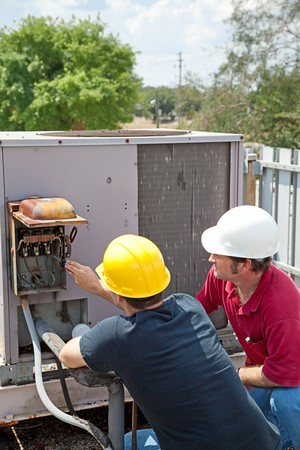 Two AC technicians on a roof repairing an industrial compressor unit. photo