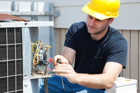 Young repairman fixing an industrial air conditioning compressor. Stock Photo - 4531535