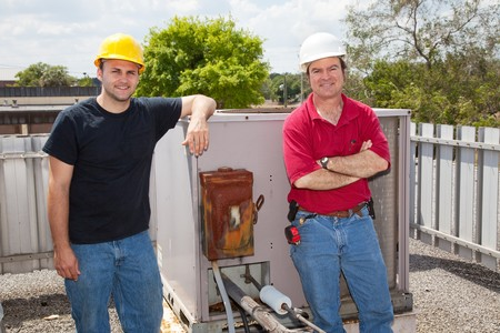 Two air conditioning repair techs standing on a roof in front of an industrial compressor unit.   photo