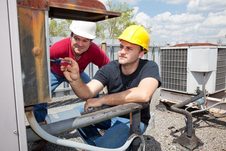 apprentice: Air conditioning repair apprentice fixes an industrial compressor unit as his supervisor watches. Stock Photo