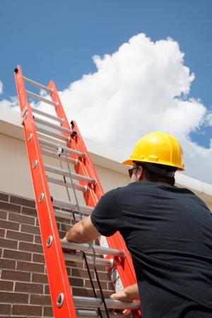 drabiny: Budowa pracownik wspinaczka drabiny do dachu. Zdjęcie Seryjne
