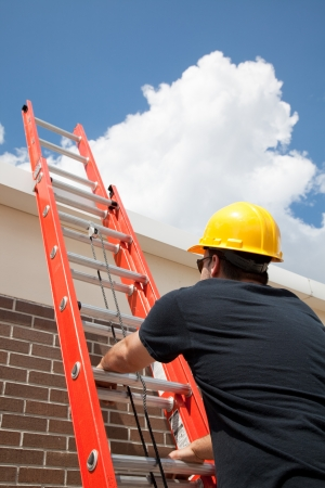 ladder safety: Construction worker climbing a ladder up to the roof.
