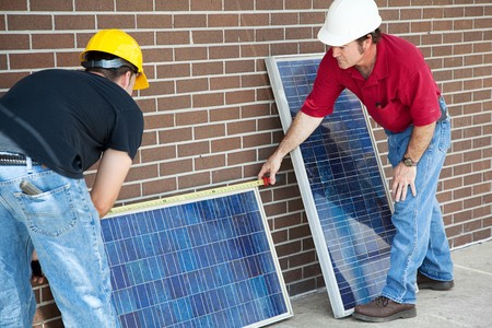 Electricians measuring solar panels they are about to install.   photo