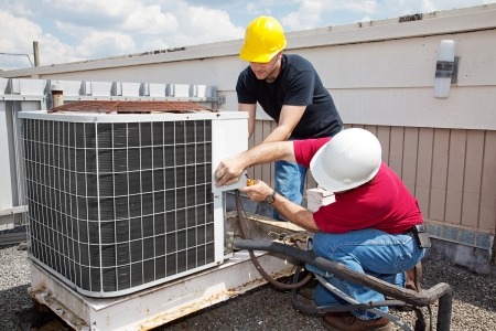 Two workers on the roof of a building working on the air conditioning unit.   Stock Photo