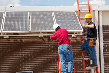 ladder safety: Two electricians installing solar panels on a building.   Stock Photo