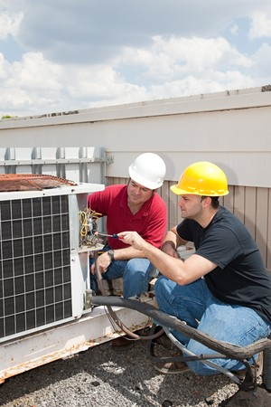 building maintenance: Instructor trains student to repair air conditioning compressor. Stock Photo