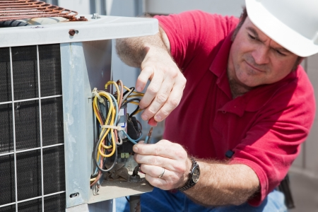 air conditioning: Air conditioning repairman rewiring a compressor unit.  Focus on the mans hands and the wires.   Stock Photo