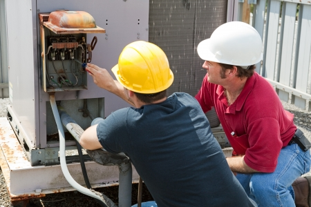 air conditioning: Two AC technicians repairing an industrial air conditioning compressor.