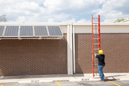 Wide angle view of a construction worker preparing to climb on to the roof of a building to work on solar panels.