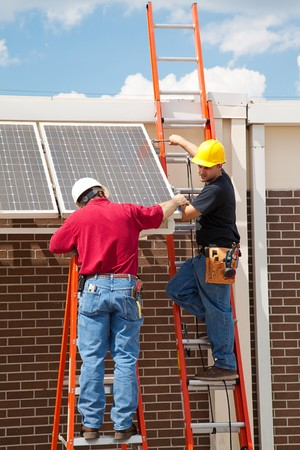 journeyman: Construction electricians installing solar panels on the side of a building.