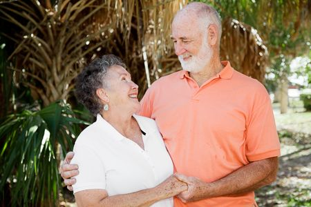 Happy senior couple holding hands and looking into each others eyes. Stock Photo - 4531412