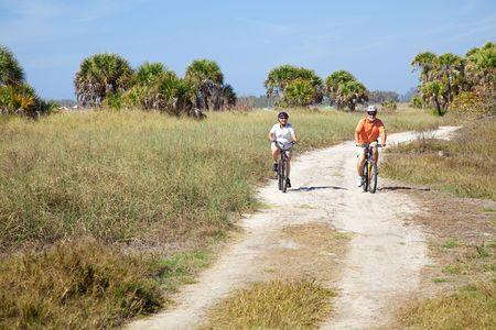 Senior couple riding their bikes on a trail beside the beach.   Stock Photo - 4531422