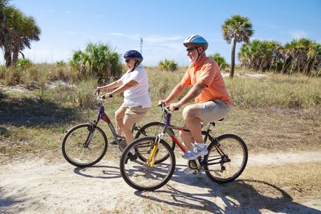 Senior couple riding bikes at the beach, wearing sunglasses and helmets.  Focus on the woman. Stock Photo - 4531415