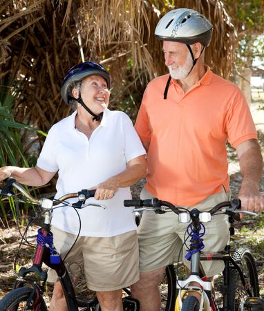 Active senior couple with their bicycles, looking lovingly at each other.   photo