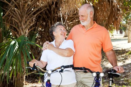 Senior couple bicycling together in the park. Stock Photo - 4531413