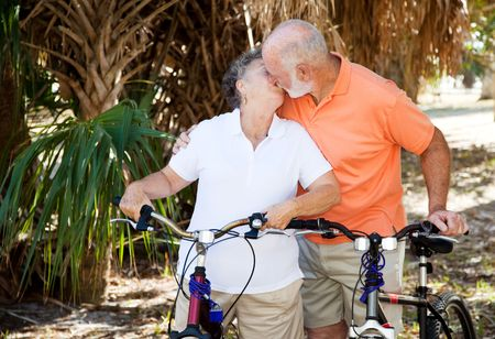 Active senior couple taking a breat from cycling to kiss each other.   photo