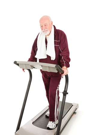 Tired senior man forcing himself to walk a treadmill to get back in shape.  Isolated on white. Stock Photo - 4566192