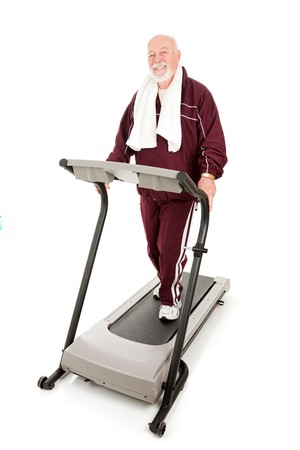 Handsome, fit senior man exercising on a treadmill.  Full body isolated. photo