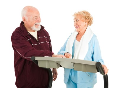 Active senior couple working out at the gym.  Isolated on white.   Stock Photo - 4564628
