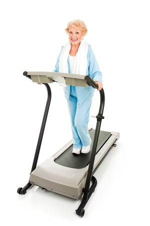 Beautiful senior woman stays fit by exercising on a treadmill.  Isolated on white.   photo