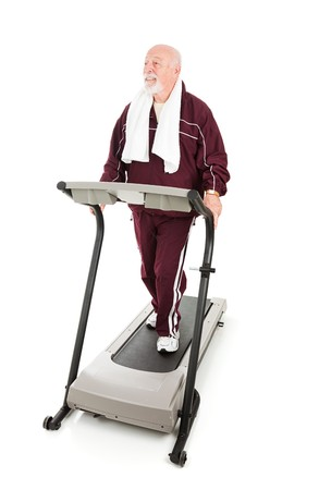Fit senior man works out on a treadmill.  Full body on white.   photo