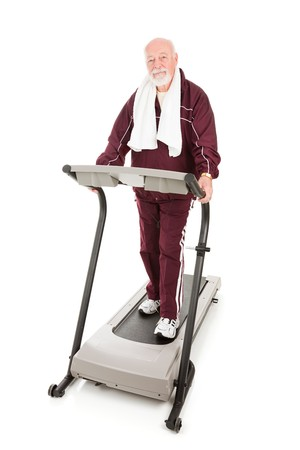 Senior man on treadmill is serious about fitness.  Isolated on white. photo