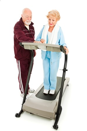 Senior man helping his wife program the treadmill.  Full body isolated. Stock Photo - 4566196