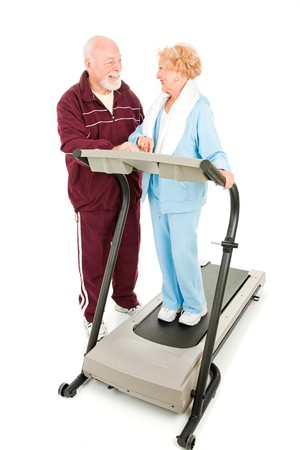 Senior man flirting with a senior woman at the gym.  Full body isolated on white.   Stock Photo - 4566195