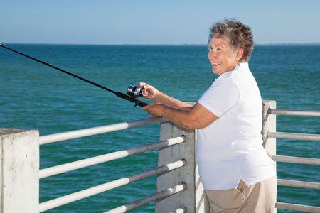 Pretty senior woman happily fishing from a pier. Reklamní fotografie