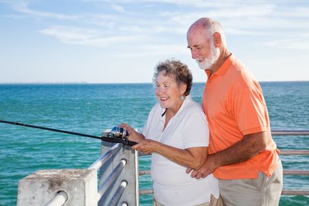 enjoys: Retired senior couple enjoys fishing together from a pier in Florida.