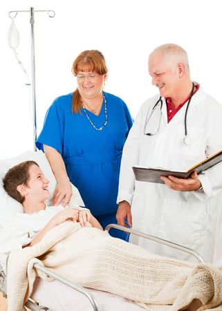 bedside: Friendly doctor and nurse caring for a young patient in the hospital.  Isolated on white.