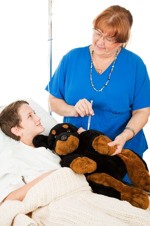 bedside: Friendly nurse pretends to give an injection to her young patients stuffed animal.  Isolated on white.