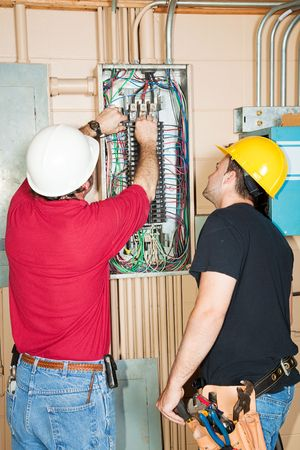 journeyman: Electrician and apprentice changing out a faulty circuit breaker in an industrial panel. Stock Photo
