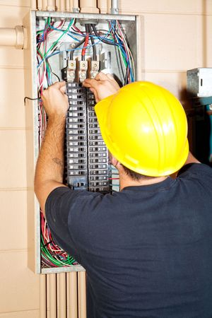 Electrician replacing a bad circuit breaker in a large industrial panel.